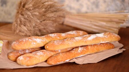 Fresh baguette on wooden table, close up.