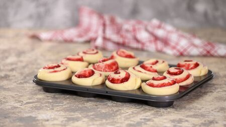 Raw yeast buns with berry jam in a baking dish. 스톡 콘텐츠
