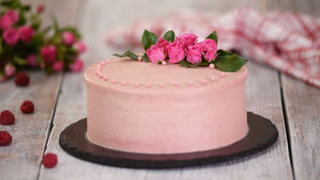 Layers cake with berry filling decorated with fresh roses.