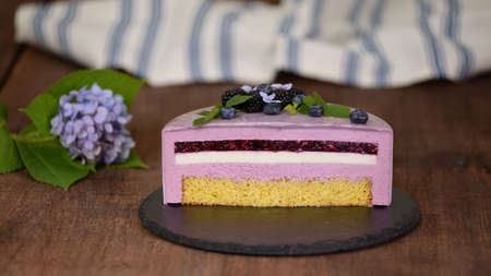 Delicious mousse cake with summer berries and mirror glaze.