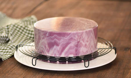 French Mousse Cake Covered With Purple Glaze. 스톡 콘텐츠
