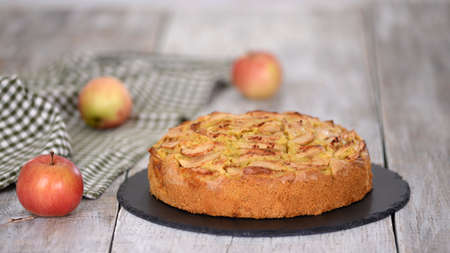 Apple pie or homemade cake with apples on wood table. Delicious apple cake.