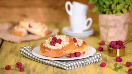 Fresh homemade open patties with cottage cheese. Traditional Russian pastry vatrushka, round buns with raspberries.