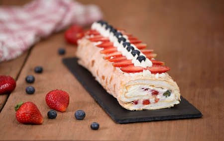Meringue roll cake decorated with blueberries and strawberries.