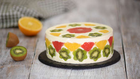 Delicious fruit mousse cake. Cake decorated with fresh fruits in jelly.