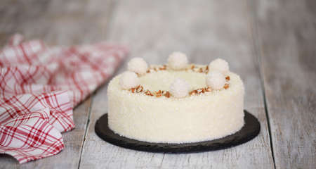Delicious coconut mousse cake, decorated with candy and almond.
