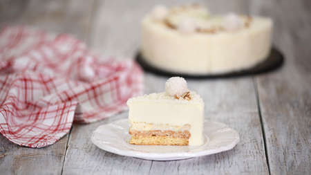 Piece of delicious coconut mousse cake with almonds.