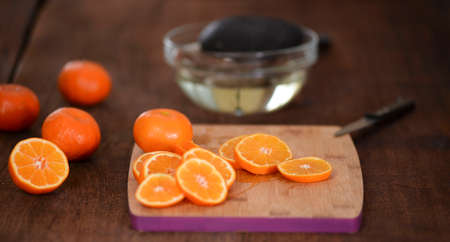 Fresh and juicy sliced tangerine on cutting board.