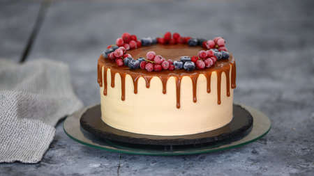 Delicious caramel cake with frozen summer berries.