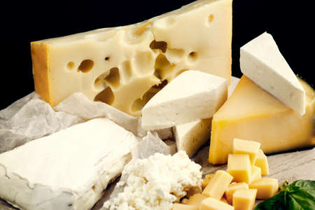 Round cheese plate, with different varieties of dairy, hard cheese (brie, home cheese, gouda, mildew cheese) with green, vertically, centered, black background, nobody