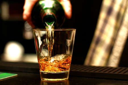 A glass cup in which hand of a bartender in a kilt pours from a bottle of alcohol (whiskey, brandy, scotch, liquor, vodka, cognac), a glass with a close standing on a wooden table