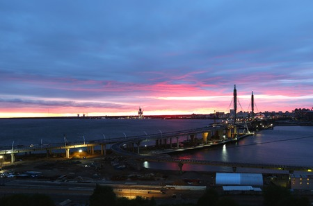 industrial district: Colourful red and blue sunset above the river with long bridge in front. Industrial district of the city