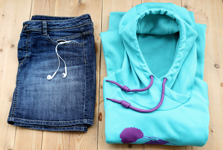 denim skirt: Outfit of casual sport woman. Blue denim skirt and light blue sweater with watch