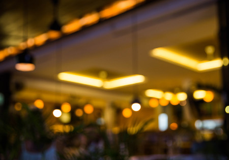 Blurred background : Restaurant with tables and chairs blur background with bokeh light. Evening time Stock Photo