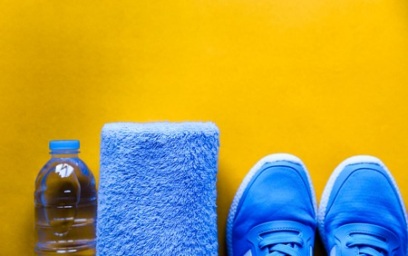 Flat lay sport shoes, bottle of water, towel on yellow background.