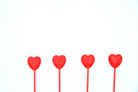 Four red heart shaped candles in a row isolated on white background. Standard-Bild