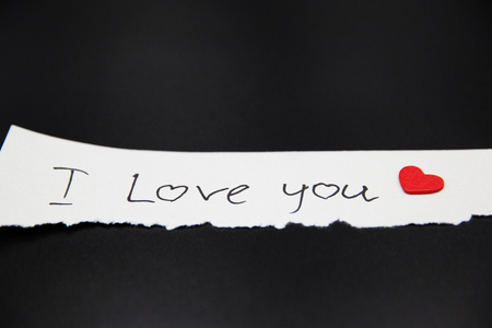 Paper message I love you on black smooth background.