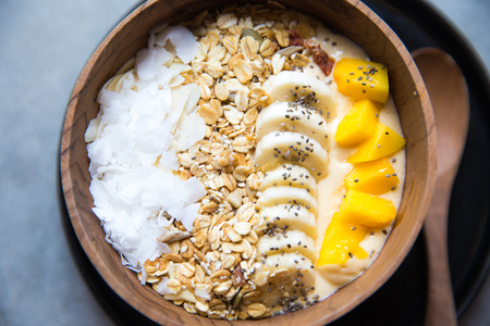 Mango smoothie bowl with strawberry and coconut and oatmeal on the table. Stockfoto