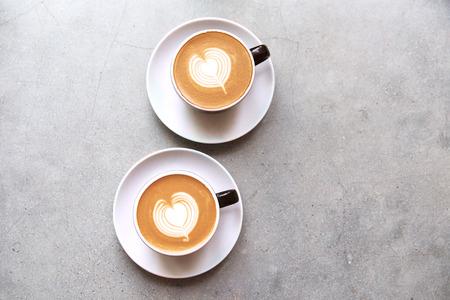 Twee zwarte kopjes lekkere cappucino met liefdeskunst latte. Stockfoto