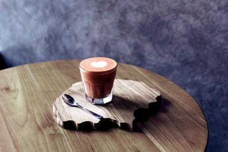 Glas leckeres letzteres mit Liebeskunst auf dem Holztisch und strukturiertem Schreibtisch. Standard-Bild