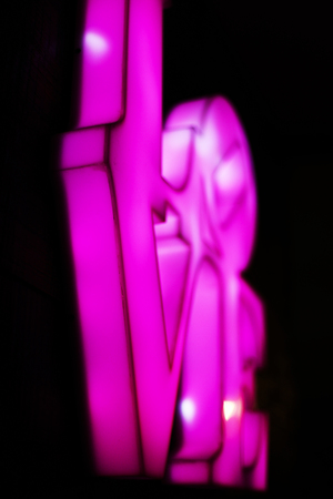 Abstact blurred Plastic pink sign of word LOVE on black background. 版權商用圖片 - 122114355