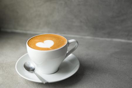 Tazza bianca di gustoso cappuccino con latte d'arte d'amore. Il giorno di San Valentino concetto. Contesto grigio cemento. Copia spazio