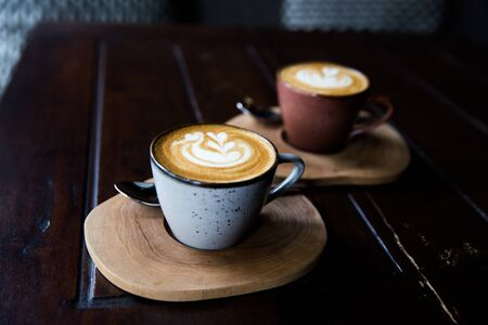 Two Cups of hot cappuccino on wooden desk with spoons on dark table background. Breakfast time.