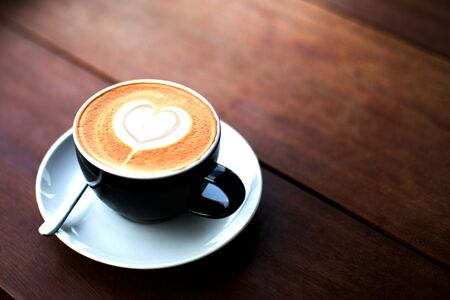 Black cup of tasty cappucino on white soucer with heart art latte. Wooden table background. 免版税图像