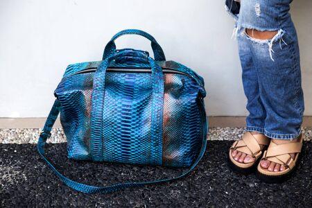 Trendy python classic blue leather big handbag closed to woman legs. Fashion accessories Reklamní fotografie
