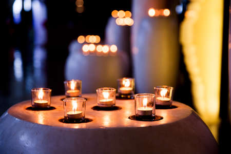 Flame of many candles burning on blurred lights background. Holiday concept.