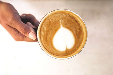 Woman is holding tasty cappucino with love art latte. Valentine's day concept. Wooden table backdrop