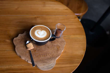 Cup of tasty cappucino with love art latte. Valentine's day concept. wooden tabele backdrop. 스톡 콘텐츠