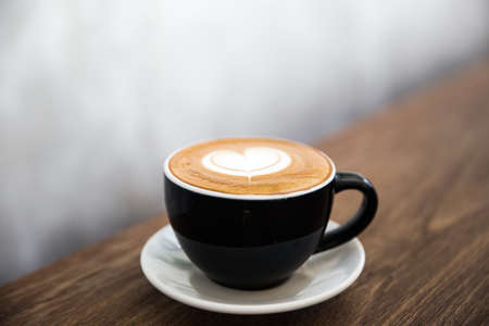 Cup of tasty cappucino with love art latte. Valentine's day concept. Wooden table backdrop closed to concrete wall. 스톡 콘텐츠