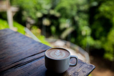 Cup of tasty cappucino on wooden table backdrop in outside cafe with green plant on background.