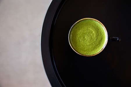 Tasty matcha drink in black cup on black table background. Healthy drink concept.