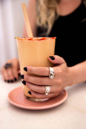 Mango banana vegan healthy smoothie with strawberry in glass in female hand with silver rings. Clean detox eating. Weight loss concept