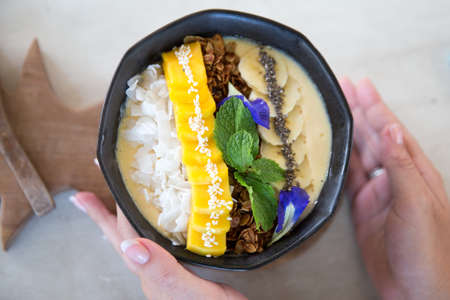 Healthy smoothie bowl with banana, granola and mint on wooden pineapple desk. Clean detox eating.