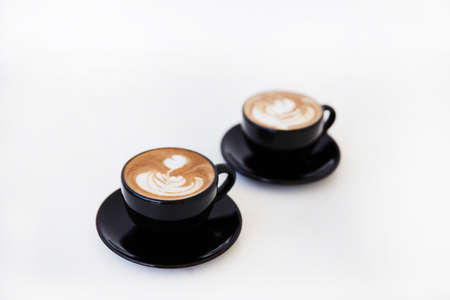 Two Cups of hot cappuccino on white wooden table background. Place for text. 스톡 콘텐츠