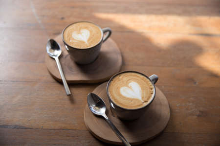 Two Cups of hot cappuccino on wooden table background. Top view. 스톡 콘텐츠