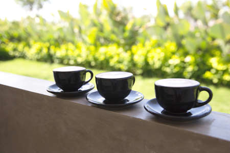 Three Cups of hot cappuccino on concrete bar table with green sunny background. Morning tropical concept