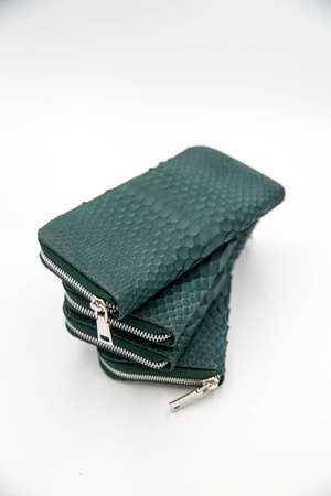 Three green snakeskin wallet purse isolated on a white background. Fashion concept 스톡 콘텐츠
