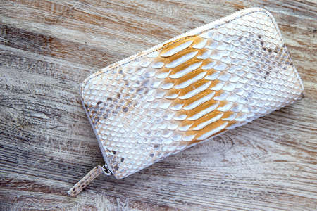 Light wallet from trendy snake python skin on wooden white background. Top view. Fashion concept. 스톡 콘텐츠