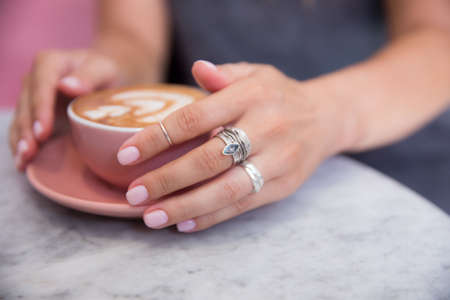 Pink trendy cup of cappuccino holding by beautiful woman's hands on marble table background. 스톡 콘텐츠