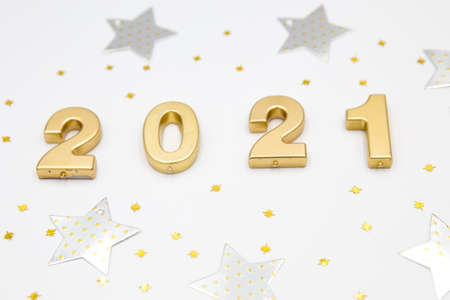 Creative Christmas and New Year composition with confetti, silver stars and 2021 numbers. Flat lay.