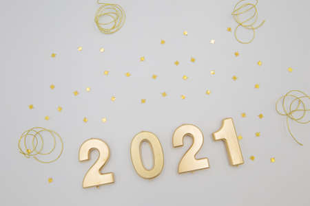 Creative Christmas and New Year composition with confetti, golden glitters and 2021 numbers. Flat lay.