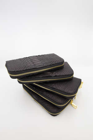 Many black snakeskin wallets purse in a row isolated on a white background. Fashion concept.