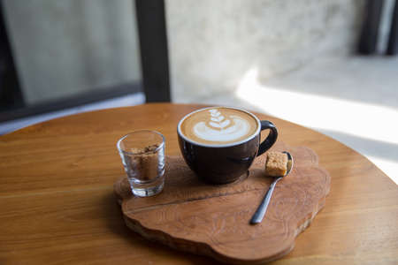 Tasty cappuccino with beautiful latte art on wooden table in the cafe. Morning concept.