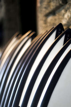 Set of black and white stylish new surf boards in a stack on concrete background. Summer sport concept