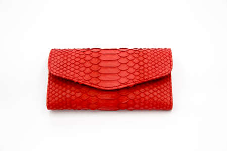 Trendy natural red snake python skin woman wallet on white isolated background. Can be used for background and wallpaper 스톡 콘텐츠