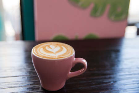 Tasty pastel pink cup of cappuccino on wooden table background. Loft urban and hipster cafe concept.